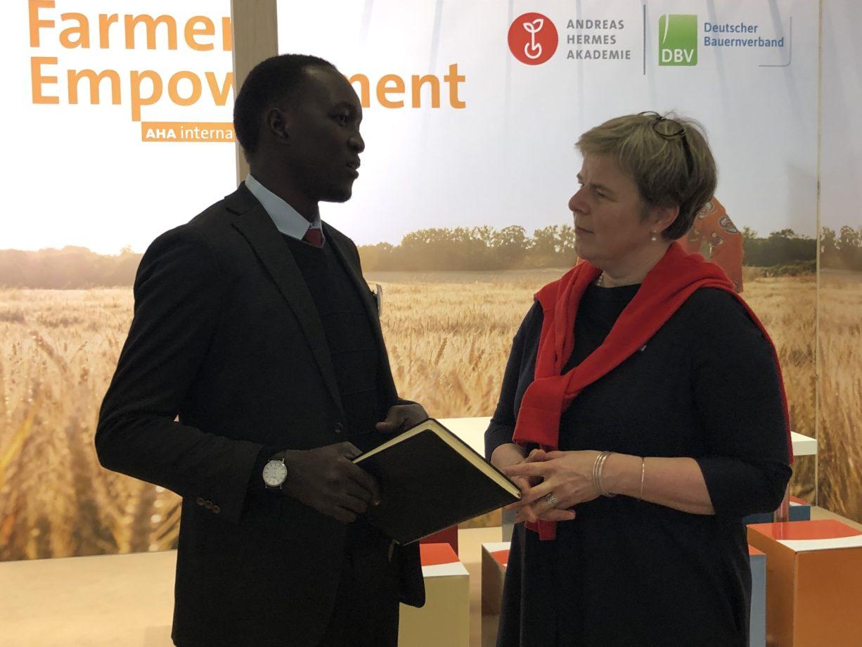 Präsident des Ugandischen Jungbauernverbands 'UNYFA', Geoffrey Okot, und AHA-Geschäftsleiterin für 'Internationale Zusammenarbeit', Nicole Bolomey, im Austausch vor dem AHA-Messestand
